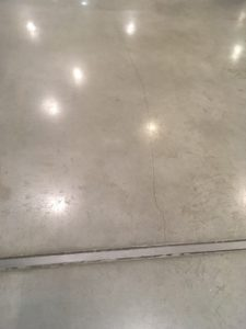 Dilation joint and cracking on a polished concrete floor in the corridor of an office building in Warsaw