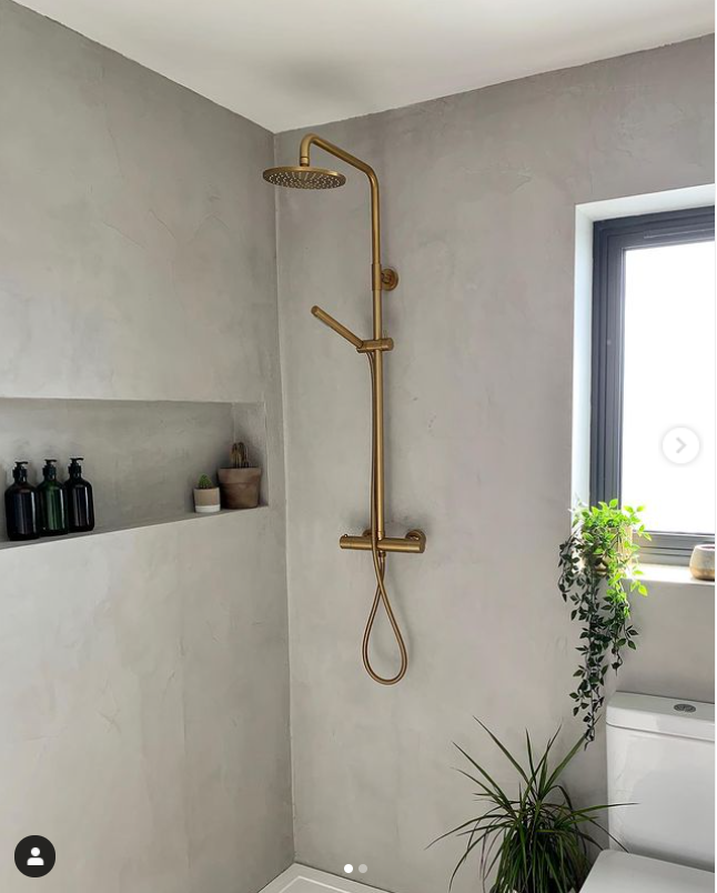 microcement bathroom with golden accessories